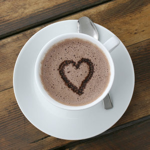 Hot chocolate heart: Heart-shaped sprinkles in a cup of hot milky chocolate.
