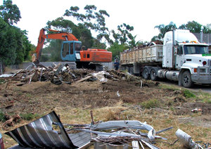demolition job: suburban house demolition and removal with excavator and truck