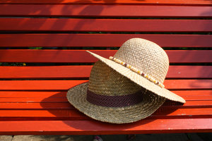 Straw hats: straw hats on a wooden bench.