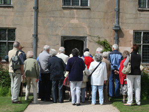 Tour group: A tour group looking at an historic house in England.