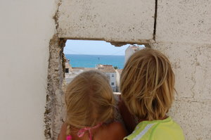 Do you sea?: A hole in a wall, two kids looking through at the sea.