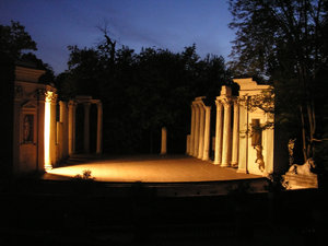 Theatre on Island: The Roman-inspired Amphitheater was built on the bank of the Łazienki lake, separated by a narrow strait from its stage. The amphitheater was built in 1790-93 by Jan Chrystian Kamsetzer. Its attic is embellished with sixteen statues representing famous p