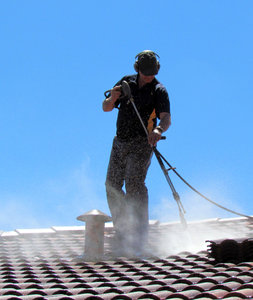 roof restoration2: workman cleaning roof tiles for restoration