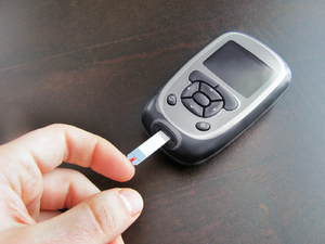 Blood glucose meter: sugar measurement by blood drop from the fingertip (diabetes check)