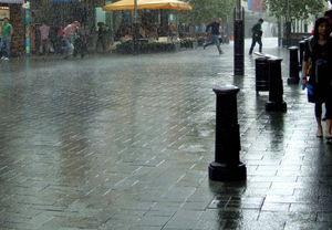running in the rain1: sunshine and rain downpour near historic city arcade