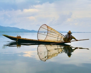 Fisherman's portrait: A fisherman fishing in his boat on Inlay lake, Myanmar.Peaceful image prepared to be your desctop wallpaper, any comments are welcome.