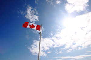 Canadian flag: Canadian flag fluttering against a blue sky on Worthing seafront