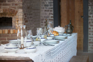 Laid table: Table laid with old flatware, plates and bowls, before the days of light bulbs