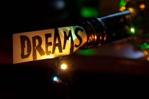 Dreams concept: Dreams concept. The word dream, bottle and multicolored lights