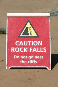 Grungy warning sign: Sign on a beach in Cornwall, England.