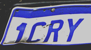 sad story ab: crumpled partial number plate of wrecked motor car